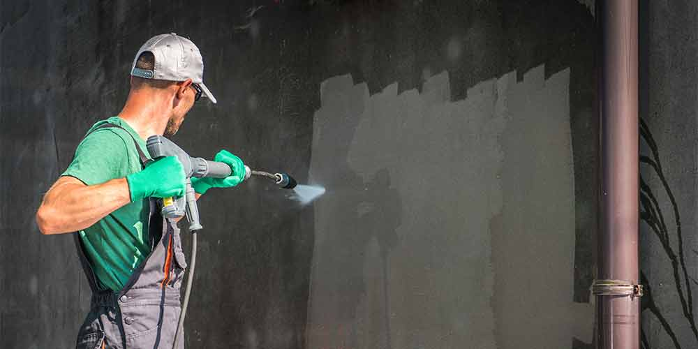 A worker pressure washes a dirty wall
