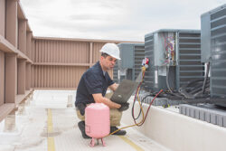 hvac technician with refrigerant working on a commercial AC on the roof