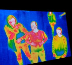 3 people seen through a thermal imaging lends with bright reds, oranges and yellows