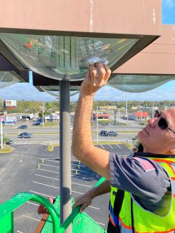 Man changing an LED lightbulb at the top of a light pole in a parking lot