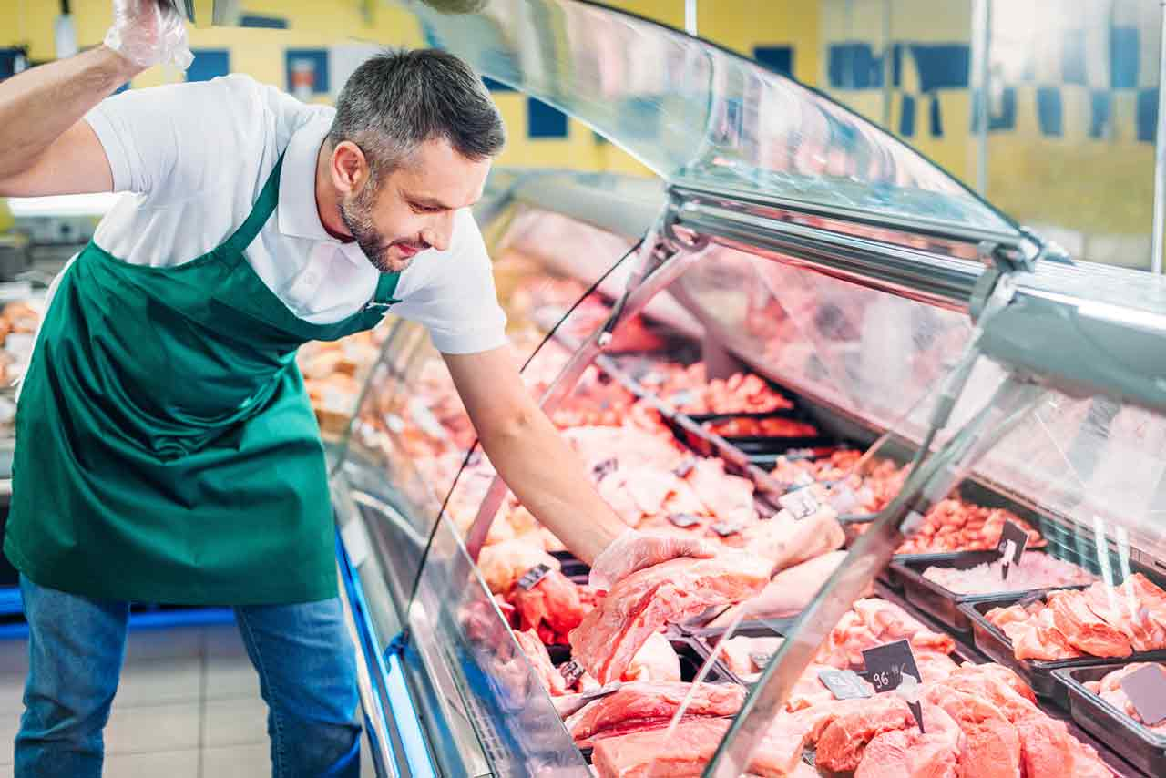 Grocery store manager leaning down into a commercial refrigeration display case full of red meat.