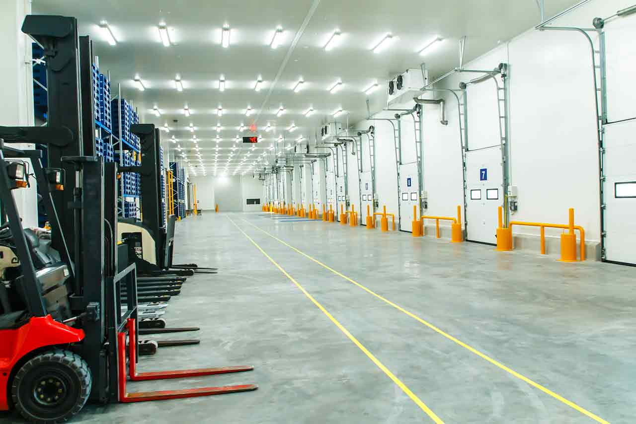 Large industrial refrigeration warehouse with forklifts and LED lights.