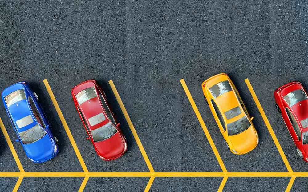 Cars parked in a well-kept parking lot with proper spacing, bright parking lot striping and great parking lot maintenance.