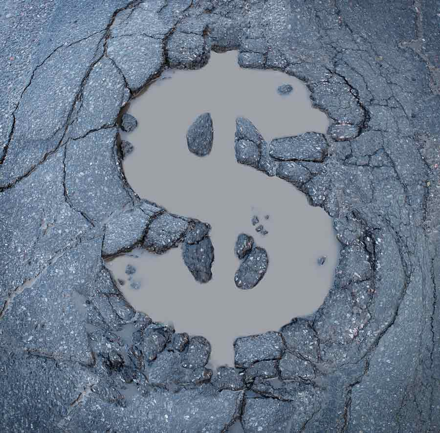 Cracked asphalt with dollar sign cutout implying major costs if you avoid fixing potholes and parking lot maintenance.